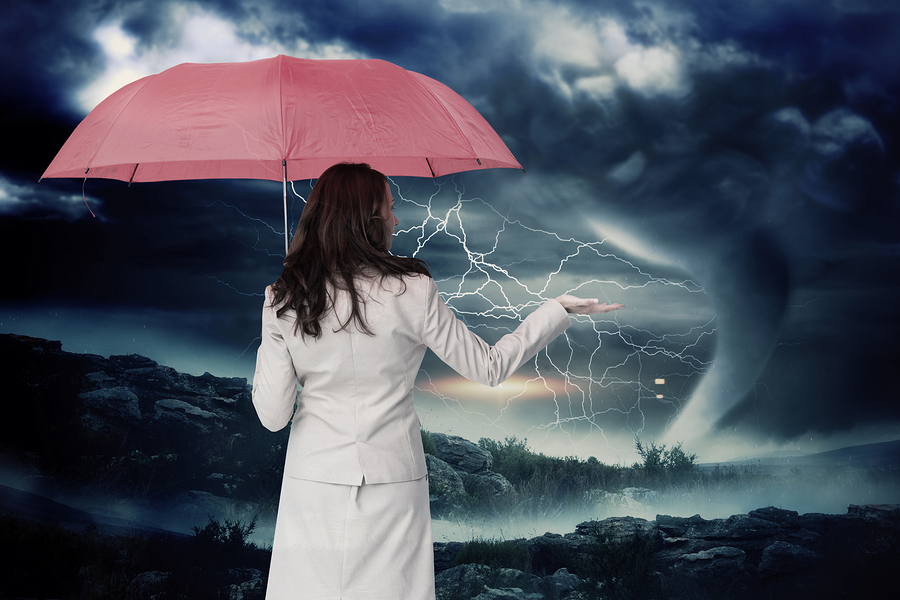 Businesswoman holding umbrella against stormy sky with tornado o