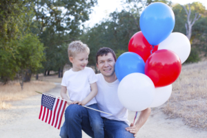 handsome father holding colorful balloons and his little son holding american flag celebrating 4th of July